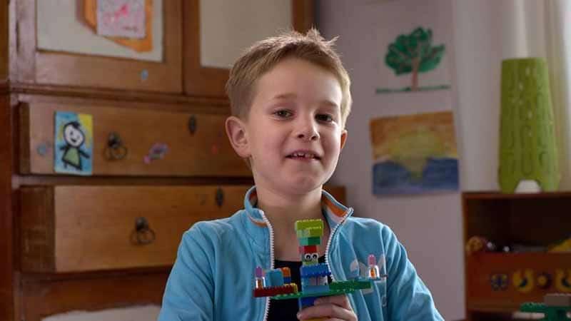 Petit garcon tenant un montage fait avec des pieces de la marque LEGO